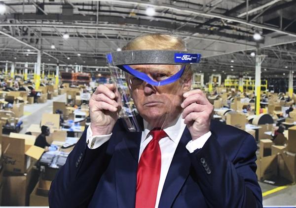 도널드 트럼프 미국 대통령이 21일(현지시각) 미시간주의 포드 자동차 로슨빌 부품공장을 시찰하며 얼굴 가리개를 들어보고 있다.