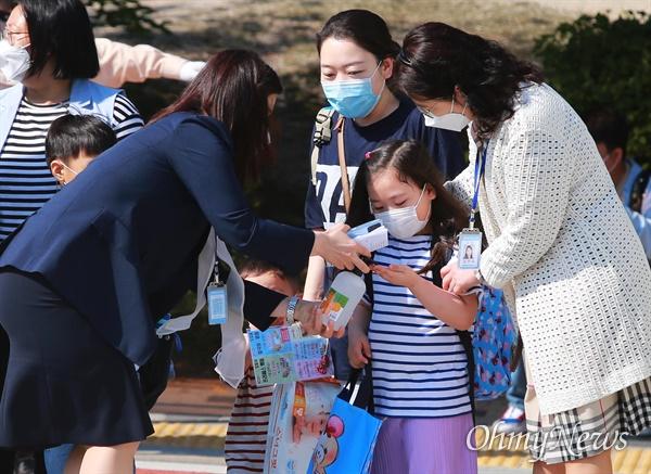 27일 오전 서울 성북구 월곡초등학교에서 1,2학년 학생들이 코로나19 여파로 인해 미뤄진 등교를 시작하고 있다. 교직원들이 교문에서 학생들에게 손소독제를 나눠주고 있다. 지난 20일 고3에 이어 27일에는 고2, 중3, 초1,2 학생들이 등교수업을 시작했다.