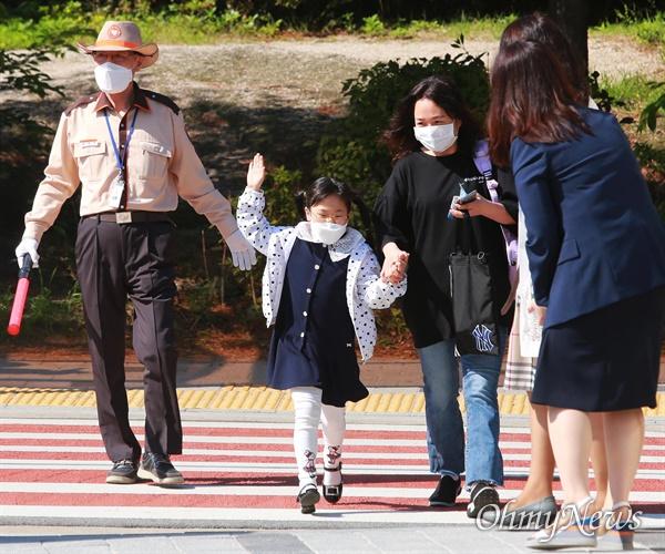 27일 오전 서울 성북구 월곡초등학교에서 1,2학년 학생들이 코로나19 여파로 인해 미뤄진 등교를 시작하고 있다. 한 학생이 손을 들고 학교앞 횡단보도를 건너고 있다. 지난 20일 고3에 이어 27일에는 고2, 중3, 초1,2 학생들이 등교수업을 시작했다.