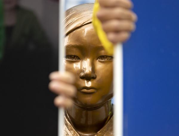 12일 서울 종로구 옛 일본대사관 앞에서 아베반일청년학생공동행동 회원들이 반일동상진상규명공대위의 소녀상 철거 및 수요집회 중단 촉구 기자회견에 맞서 소녀상을 보호하고 있다.