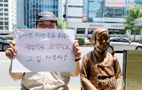 27일 부산 일본영사관 평화의소녀상 앞에서 53차 수요시위가 열린 가운데, 한 참가자가 <조선일보> 보도를 비판하는 피켓을 들고 있다.