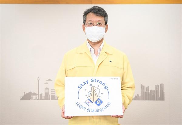 """'스테이 스트롱(Stay Strong) 캠페인'에 참여한 변성완 부산시장 권한대행이 """"다 함께 힘내 보입시더"""" 피켓을 들고 있다."""