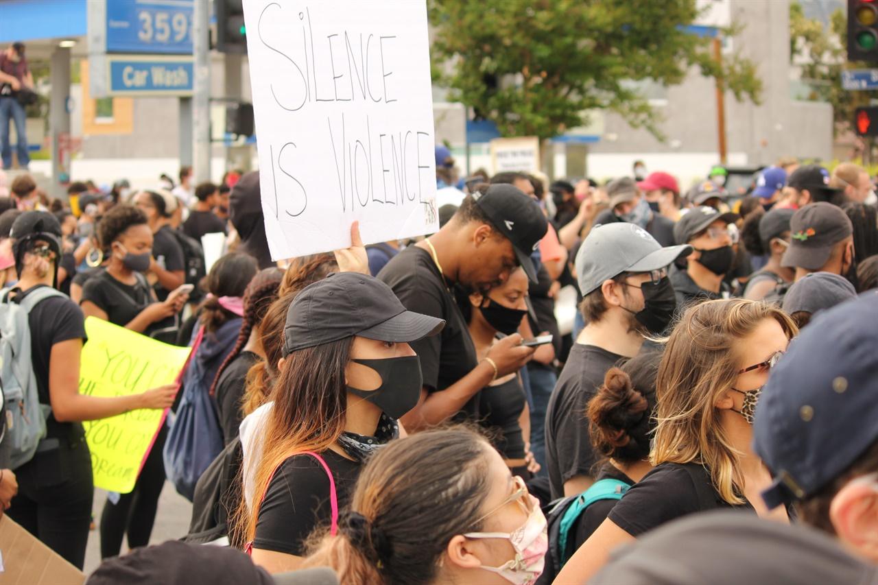 한 시위자가 '침묵하는 자도 공범이다'라는 피켓을 들고 있다.