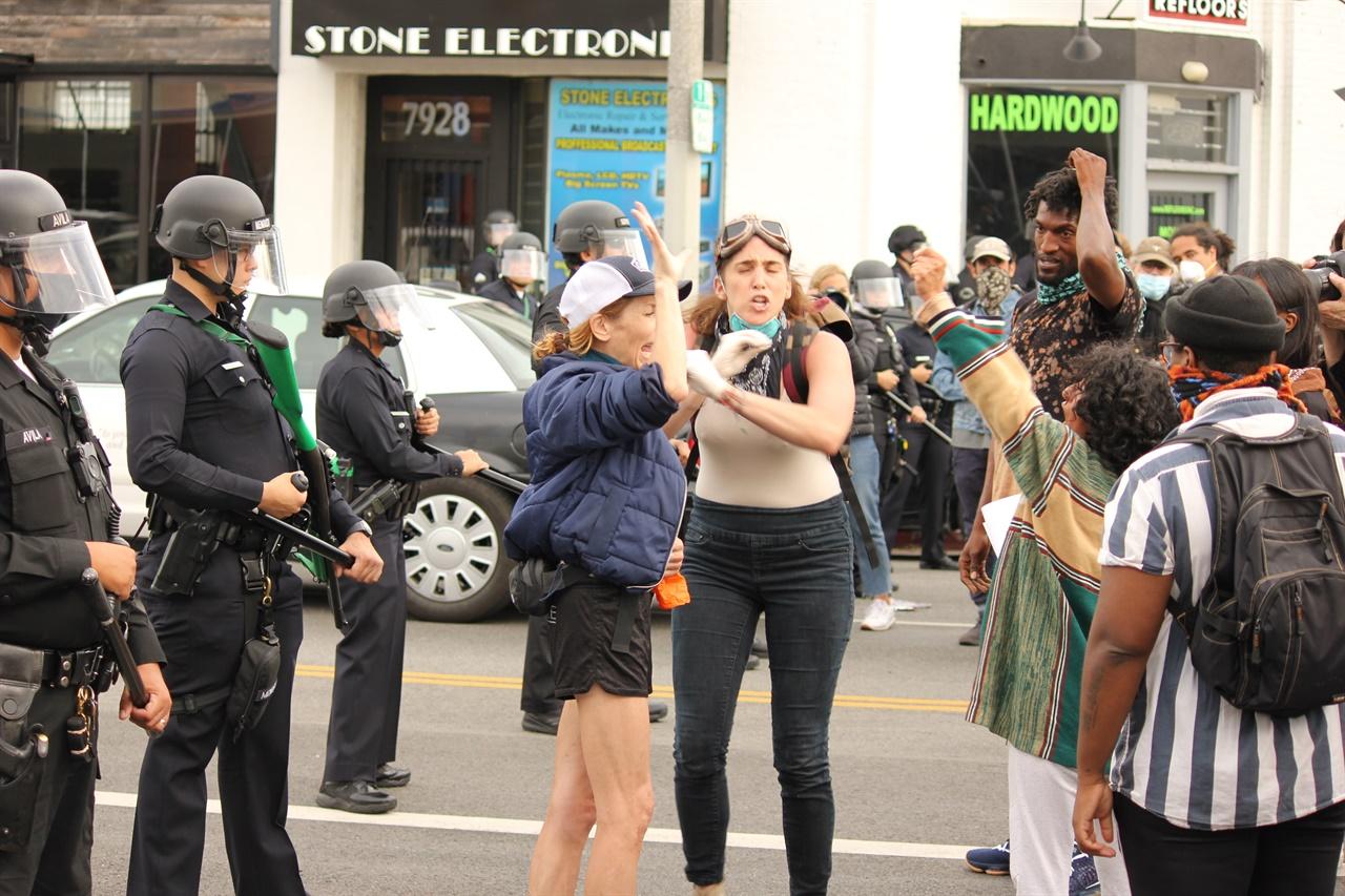 경찰 저지선을 뚫자고 선동하는 시위 참석자를 다른 참석자들이 설득하고 있다.