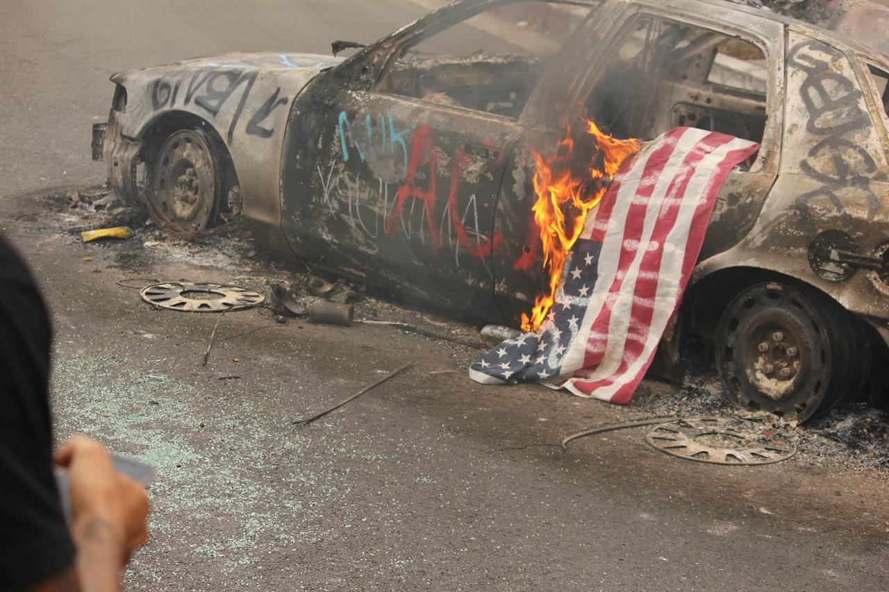 시위대에 의해 차량과 성조기가 불타고 있다.