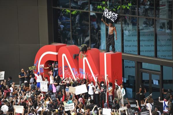 애틀랜타 CNN 본사 앞 '흑인 사망' 항의 시위대 5월 29일(현지시간) 미국 조지아주 애틀랜타의 CNN 본사 앞에서 흑인 남성 조지 플로이드가 경찰의 가혹 행위로 숨진 사건에 항의하는 시위가 벌어진 가운데 한 시위 참가자가 'CNN' 로고 조형물 위에 올라가 '흑인의 생명도 중요하다'(Black lives matter)고 쓰인 깃발을 흔들고 있다.