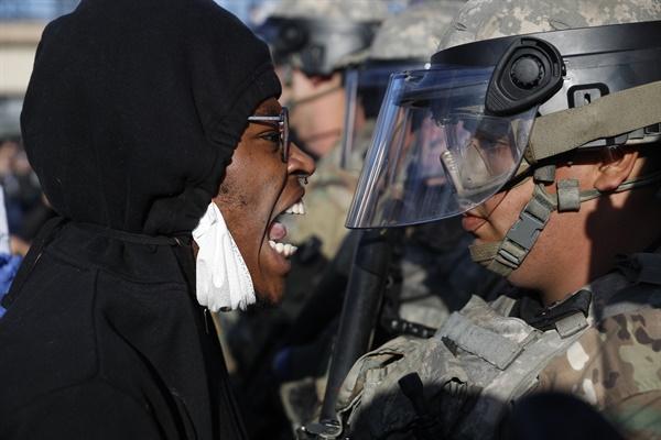 미국의 흑인 남성 조지 플로이드의 사망 사건에 분노한 시위대가 29일(현지시간) 미네소타주 미니애폴리스의 시위 현장에 배치된 주 방위군을 향해 소리를 지르고 있다.