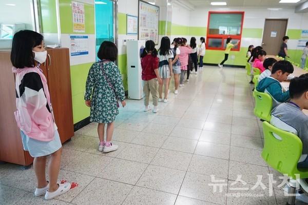 급식소 바닥에 붙여진 스티커에 맞춰 거리를 유지한 채 줄서있는 초등학생들.