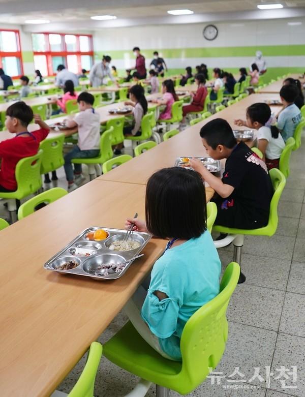 한 방향으로 앉아 점심을 먹고 있고 있는 초등학생들.
