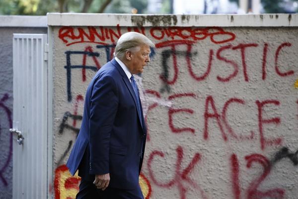 도널드 트럼프 미국 대통령이 1일(현지시간) 워싱턴DC 백악관을 나와 라파예트 공원을 지나 '대통령의 교회'로 불리는 인근 세인트 존스 교회로 걸어가고 있다. 트럼프 대통령 옆의 건물 벽에 흑인 남성 조지 플로이드 사망 사건에 항의하는 시위대의 낙서가 적혀 있다.