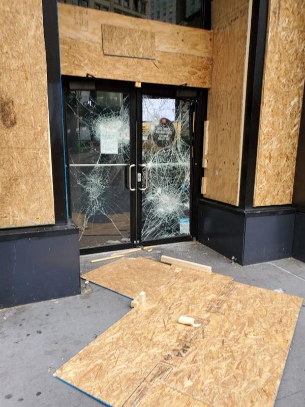 맨해튼의 한 상점이 약탈 파괴 행위를 막기 위해 널빤지로 창문과 출입구를 막고 있는 모습