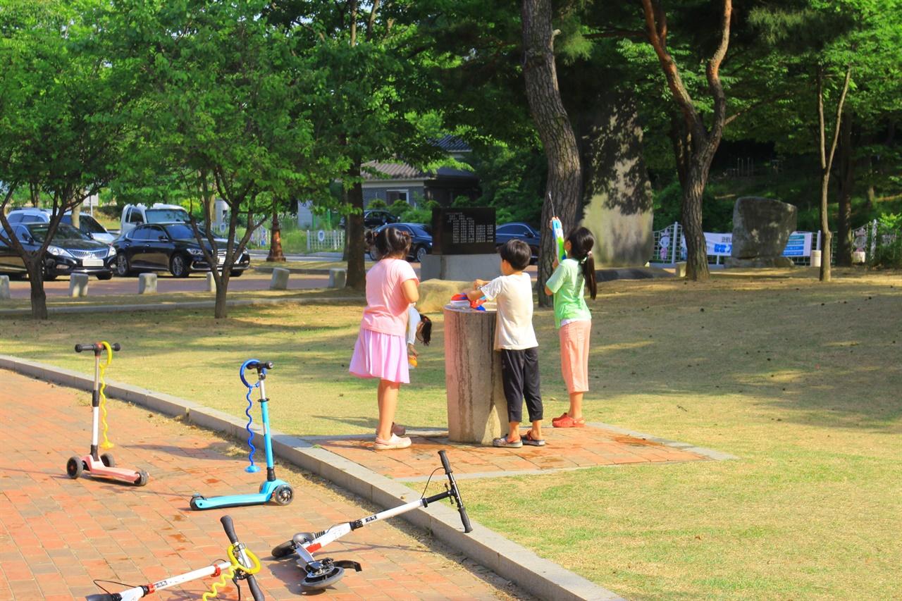 일찍 수업을 마친 초등학생들이 킥보드를 타다 더웠는지 공원 음수대에서 물장난을 하고 있는 모습