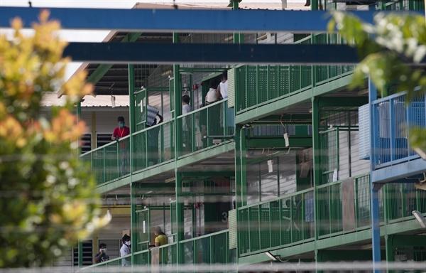 코로나19 확진자 다수 발생한 싱가포르 이주노동자 기숙사 코로나19 확진자가 다수 발생해 격리지역으로 선포된 싱가포르의 한 이주노동자 기숙사에서 4월 21일 거주자들이 방에 머물지 않고 복도에 나와 있다.