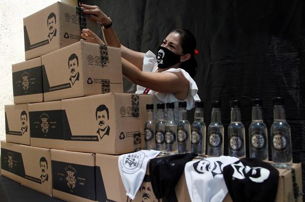 지난 4월 16일 멕시코 잘리스코 주 과달라하라에서 한 여성이 유명 마약왕 호아킨 '엘 차포' 구즈만토의 얼굴이 그려진 상자들을 정리하고 있다. 이 상자에는 이 지역 취약계층에게 보급할 물자들이 담겨 있다.