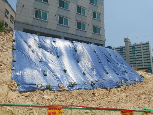 울산 동구 남목원룸을 지탱하다 깎여 나간 경사진 언덕에 동구청이 물이 스며드는 것을 막기 위해 방수포를 덮어놓았다.