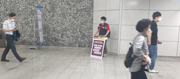 9호선 공영화하라! 9호선 2, 3단계 구간에서 일하는 노동자가 서울시의 '민간위탁 동의안'에 반대하며 1인 시위를 하고 있다.