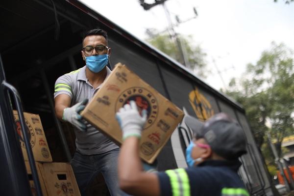 2020년 6월 1일 멕시코 멕시코시티에서 노동자 두 명이 맥주 상자를 하역하고 있다. 이날 멕시코는 비필수산업 재개를 포함한 순차적 정상화 조치를 시작했다.
