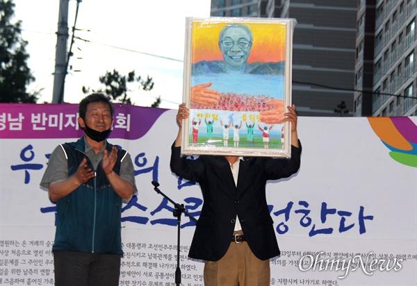 """6.15경남본부는 6월 15일 저녁 창원 정우상가 앞에서 """"6.15공동선언 20주년 기념식, 경남 반미자주대회""""를 열었다. 김영만 고문이 신미란 작가가 그린 그림을 선물로 받은 뒤 들어 보이고 있다."""