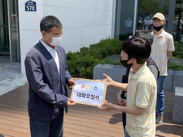 박정훈 라이더유니온 위원장이 쿠팡 관계자에게 '대화요청서'를 전달하고 있다.