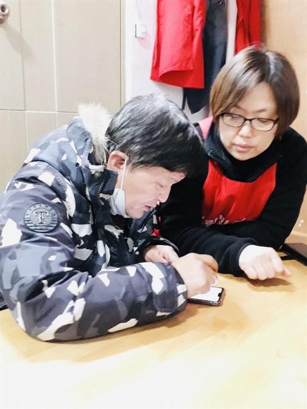 주민에게 핸드폰 사용법을 알려주고 있는 박승민.