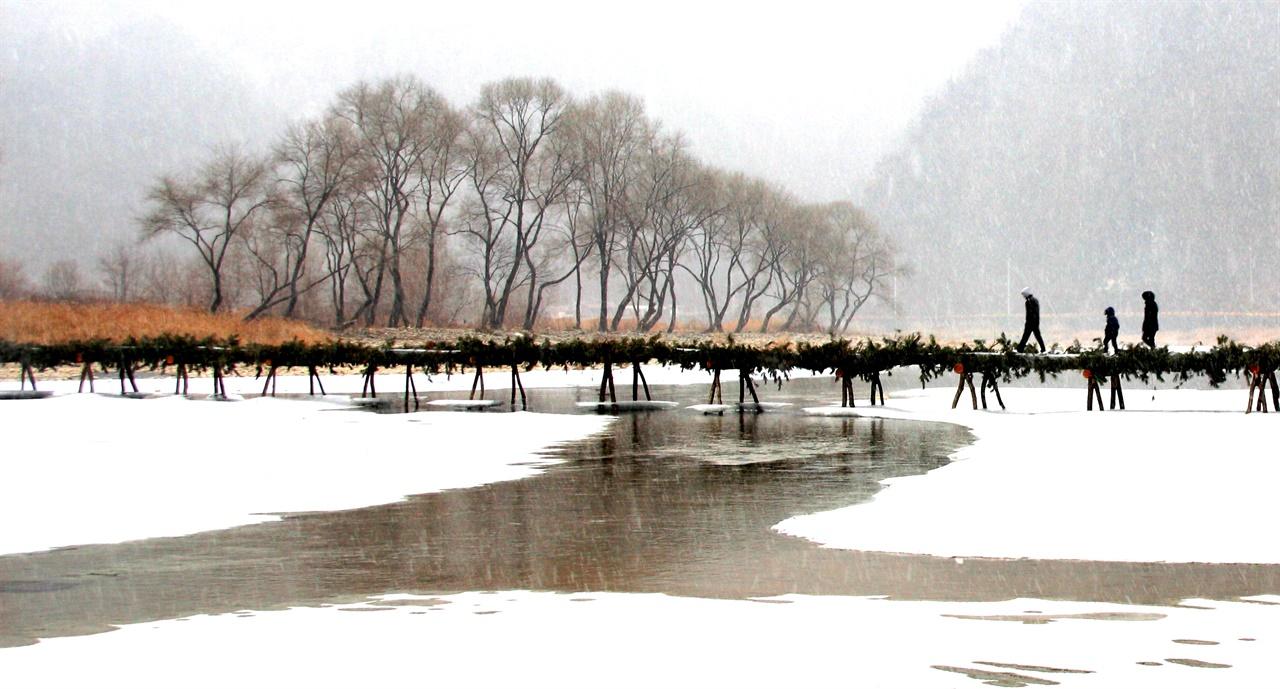 눈 내리는 겨울, 다리를 건너는 사람들. 눈보라가 날리는 강가, 섶다리를 건너 어딘가로 가고 있는 사람들.