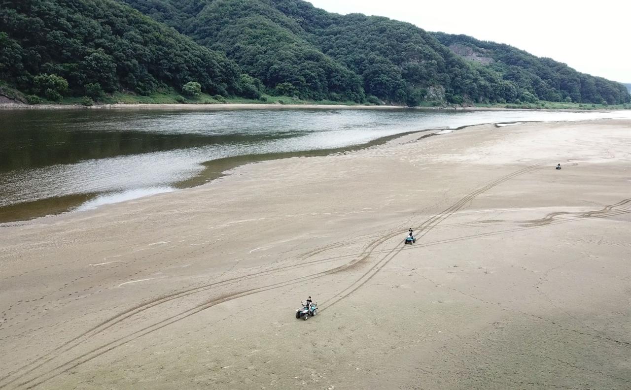 백제보 수문개방으로 상류에 생겨난 유구천 합수부 모래톱에서 사륜 오토바이들이 강변을 휘젓고 다닌다.