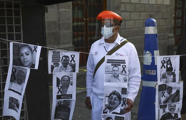 지난 5월 29일 멕시코시티의 국립궁전 앞에서 열린 시위 도중 한 병원 노동자가 코로나19로 사망한 동료들의 사진과 함께 서있다. 이날 멕시코 전역의 공공병원에서는 코로나19로 인한 의료진 감염과 사망에 항의하는 시위가 벌어졌다.
