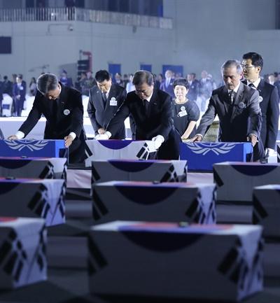 문재인 대통령이 25일 서울공항에서 열린 6·25전쟁 70주년 행사에서 국군 전사자들의 유해에 참전기장을 수여한 뒤 묵념하고 있다.