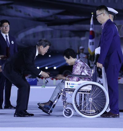 문재인 대통령이 25일 서울공항에서 열린 6·25전쟁 70주년 행사에서 참전용사 유족에게 무공훈장을 수여하고 있다.