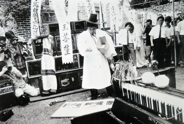 백남준 I '보이스 추모굿' 1990년. 백남준 상징인 TV와 피아노 그리고 보이스 상징인 모자가 보인다.