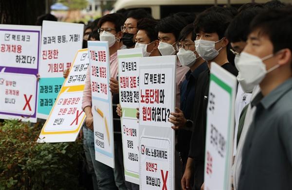 인천국제공항공사노동조합 소속 조합원들이 25일 오후 서울 청와대 인근에서 열린 기자회견에서 비정규직 보안검색 요원들의 정규직 전환 관련 입장을 발표하며 손팻말을 들고 있다.