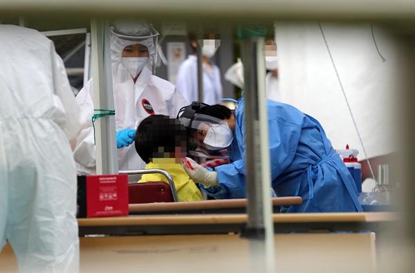 30일 오전 대전시 동구 가오동 동구보건소에 마련된 신종 코로나바이러스 감염증(코로나19) 선별진료소에서 확진자와 접촉한 초등학생들이 가족과 함께 검사 순서를 기다리고 있다. 2020.6.30