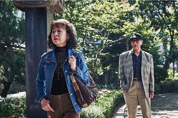 """나랑 연애할래요? 공원에서 바카스를 들이밀며 """"나랑 연애할래요?"""" 묻는 일명 '바카스 할머니' 역의 윤여정과 그 뒤를 홀린 듯 따라가는 손님."""