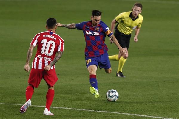 바르셀로나의 리오넬 메시(가운데)가 7월 1일(한국시간) 스페인 바르셀로나의 캄프 누 경기장에서 열린 FC바르셀로나와 아틀레티코 마드리드의 스페인 프리메라리가 축구 경기 도중 아틀레티코 마드리드의 엔젤 코레아 앞에서 공을 차고 있다.