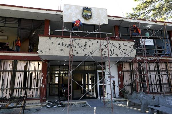 지난 2019년 12월 2일 월요일 멕시코 빌라 유니언에서 청소 노동자가 총알 구멍이 난 시청의 외관을 수리하고 있다. 이곳에서는 중무장한 마약조직 카르텔 공격조직과 보안군 사이의 주말 총격전이 벌어져 22명이 숨졌다.