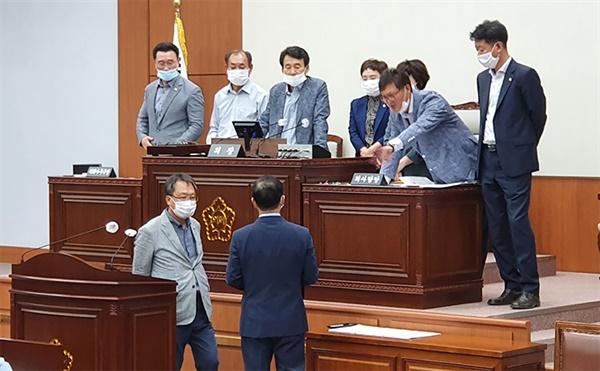 1일 강릉시의회 후반기 원구성을 위한 본회의장에서, 민주당 의원들이 의장석을 점거한 채 원구성 협의에 나설 것을 촉구하고 있다.