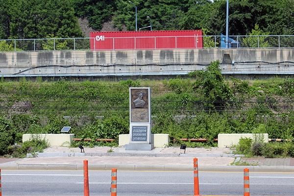철길 위쪽 길가에 세워져 있는 '원태우 지사 의거지' 표지석이 멀리 보이는 풍경. 사진의 표지석과 붉은 지붕 건물 사이가 철길이다.