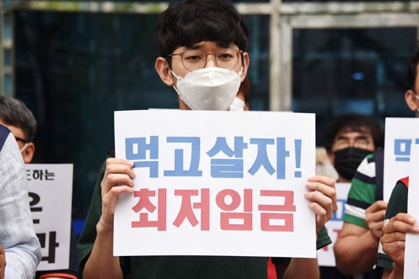 김성훈 부산청년유니온 위원장이 2일 부산시 동구 부산경총 앞에서 하루 전 경영계의 최저임금 삭감안에 반발하는 규탄 피켓을 들고 있다.
