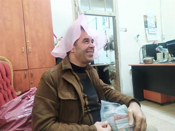 팔레스타인평화연대 활동가가 선물한 상보를 머리에 써 보는 와엘 친구들이 상보를 선물하자 와엘이 익살스럽게 모자냐고 하며 머리에 써보고 있다