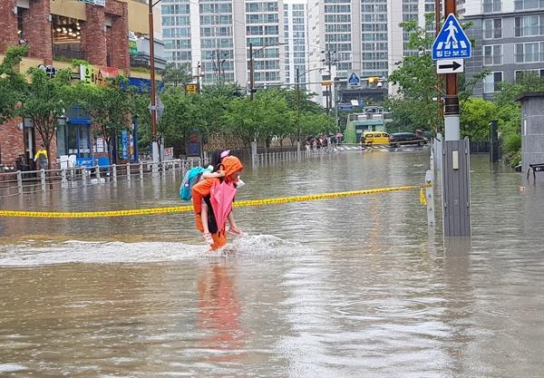 10일 호우경보로 부산에 많은 비가 내린 가운데, 부산 연제구의 한 아파트 인근 도로가 물에 잠기자 한 소방대원이 초등학생을 업고 길을 건너고 있다.