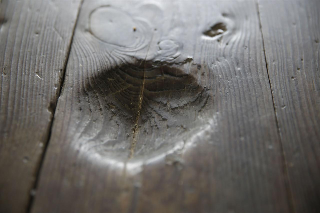 옛 선비들이 쓰던 물벼루. 움푹 파인 바닥에 물을 담아두고 붓끝에 물을 찍어서 마룻바닥에 글을 쓰고 그림을 그린 흔적이다.