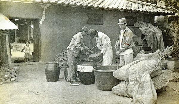 1970년대 농민들이 집 마당에서 볍씨소독을 하고 있다. 지금은 중년이 됐을, 대문턱에서 바라보는 아이의 모습이 정겹다.