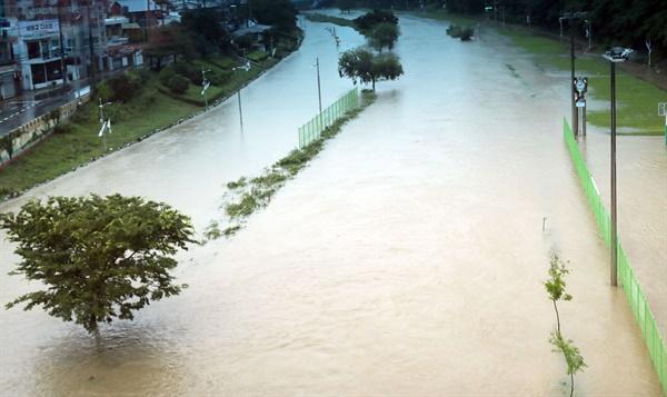 지난 13일 호우 특보가 내려진 부산 동래구 온천천 산책로가 불어난 물에 잠겨 있다. 집중 호우로 동래 연안교, 세병교, 수연교 하부도로가 침수돼 현재 통제된 상태다.