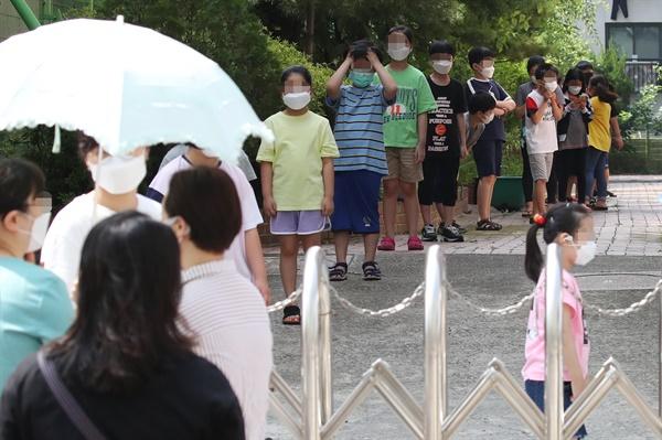 코로나19 검사 받으러 길게 줄지어 선 초등학생들 5일 서울 중랑구 묵현초등학교에 마련된 임시 선별진료소에서 학생들이 검사를 받기 위해 길게 줄지어 서 있다. 서울 중랑구는 묵현초 학생 1명이 신종 코로나바이러스 감염증(코로나19) 확진 판정을 받았다고 전날 밝혔다.