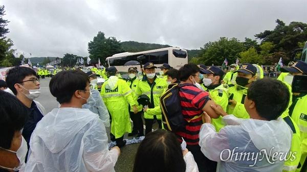 15일 오전 11시 20분께 고 백선엽의 운구차가 대전현충원 정문에 들어서자 현충원 안장에 반대하는 시위대가 운구차를 막기 위해 뛰어들다 경찰의 제지를 받고 있다.