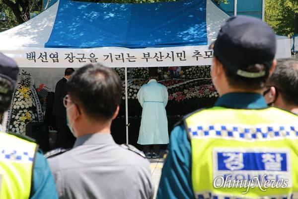 부산시청 광장에 마련된 고 백선엽 장군 부산시민 추모분향소를 둘러싸고 16일 진보단체가 규탄 기자회견에 나서자 경찰이 배치됐다. '경찰벽' 뒤로 추모행렬이 이어지고 있다.