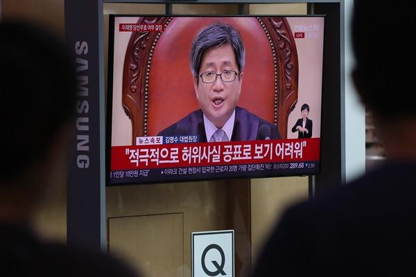 16일 서울역에서 시민들이 이재명 경기도지사에 대한 상고심 선고 공판 뉴스를 시청하고 있다.