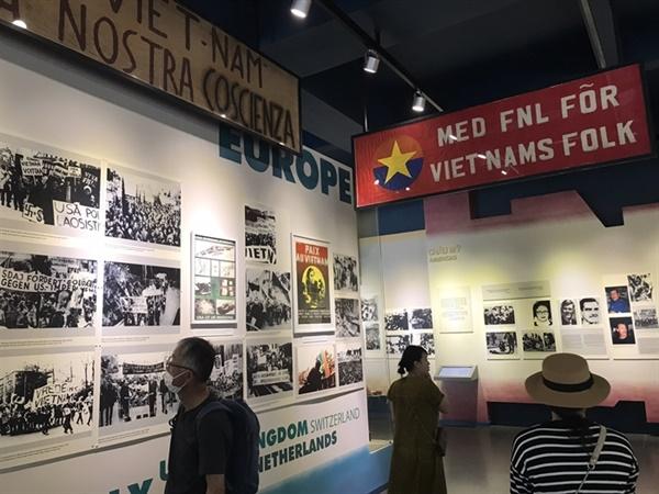 전쟁 박물관 내부 게시물들을 살펴보는 관람객들