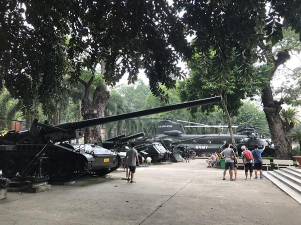 호찌민 전쟁 박물관 외부  전시되어 있는 탱크를 살펴보는 관람객.