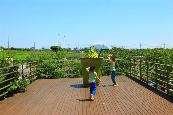 제주 오설록 티 뮤지엄 앞 녹차 아이스크림 조형물에서 점프 샷을 즐기는 어린이들 모습
